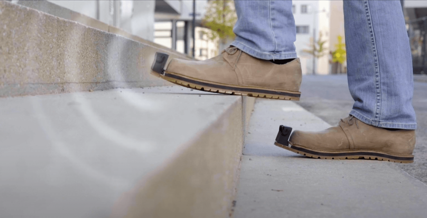 Image: InnoMake on brown shoes, man walking up steps, waves in front of shoe